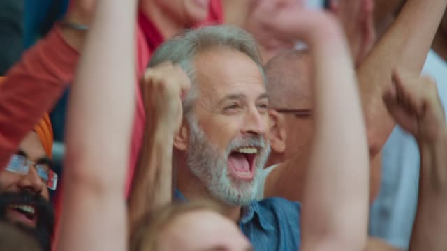 senior man with grey beard loudly celebrating the score on the stadium tribune - fan enthusiast stock videos & royalty-free footage