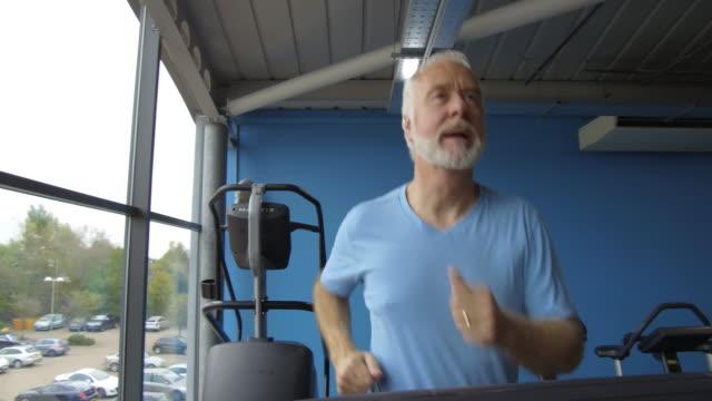 Senior man with grey hair and beard on running machine