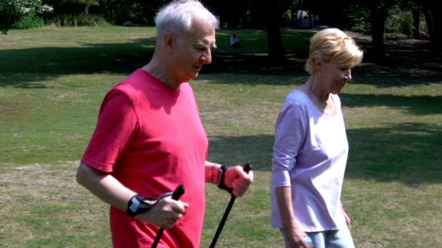 公園で女性が歩いている棒をハイキングと年配の男性 - パワーウォーキング点の映像素材/bロール