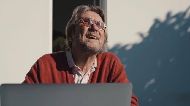 senior man with laptop enjoying sun on patio - e mail stock videos & royalty-free footage