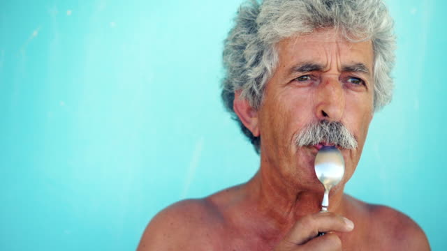 Senior man with spoon in mouth
