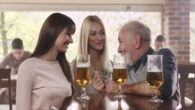 senior man with two young woman in bar - lager stock videos & royalty-free footage
