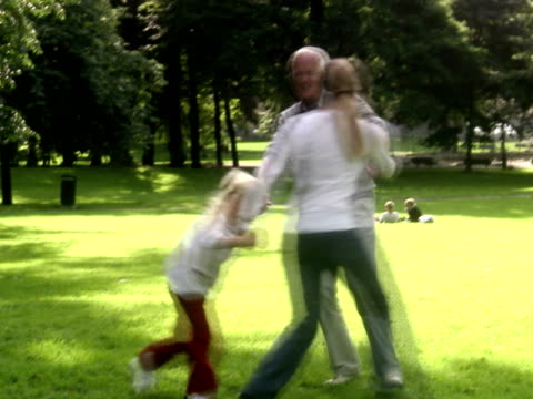 Senior man woman and child dancing in a park Sweden.