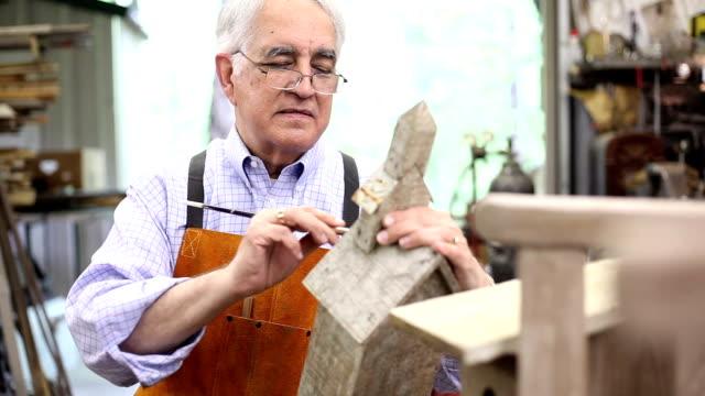 senior man working alone in his workshop. - birdhouse stock videos & royalty-free footage