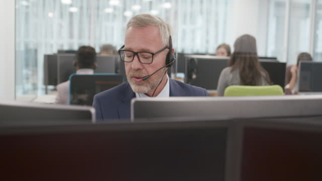 senior man working as customer support in call center - facial hair stock videos & royalty-free footage