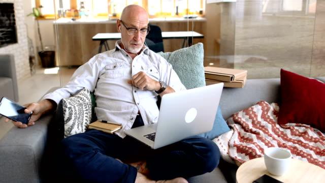 vidéos et rushes de homme aîné travaillant à la maison - seniornaute