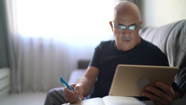 vídeos de stock, filmes e b-roll de idoso trabalhando / fazendo algumas anotações em casa - sala de estar