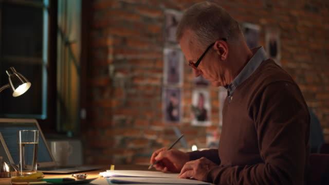 vidéos et rushes de ds homme senior travaillant dans le bureau de nuit - 50 54 ans