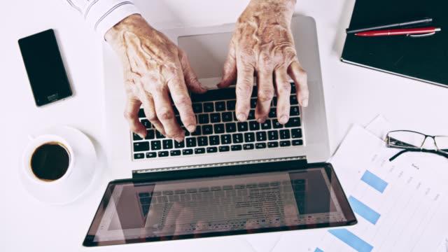 vídeos y material grabado en eventos de stock de ha altos hombre trabajando en un ordenador portátil en la oficina - trabajo de oficina