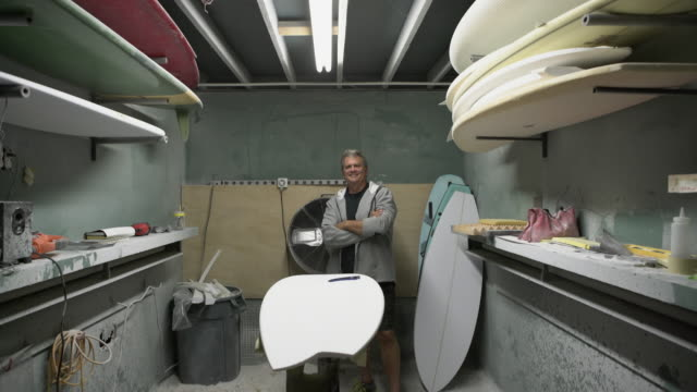 vidéos et rushes de ws senior man working on a surfboard in his workshop - groupe d'objets