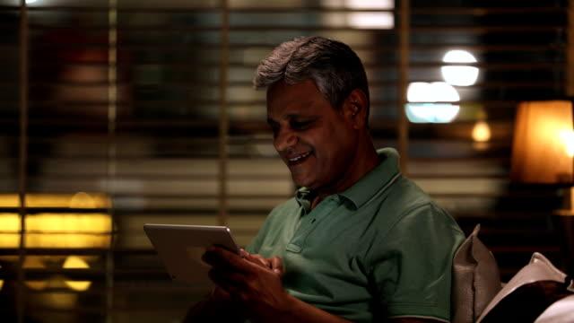 vídeos de stock e filmes b-roll de senior man working on digital tablet at night, delhi, india - idoso na internet