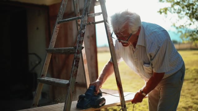 senior man working on his weekend house - ladder stock videos & royalty-free footage