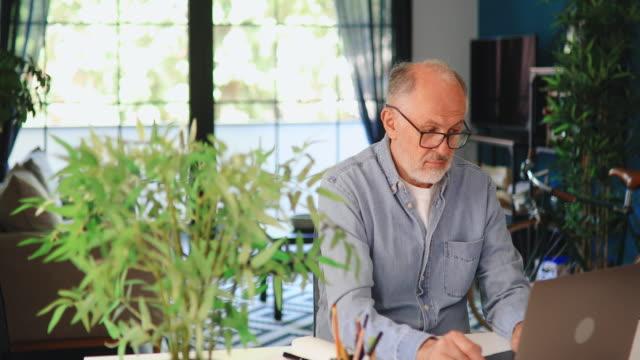 senior-mann arbeitet online von zu hause aus - erwachsener über 40 stock-videos und b-roll-filmmaterial