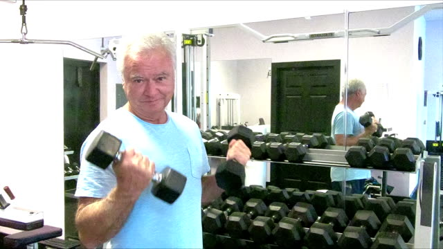 Senior man working out at the gym, lifting handweights
