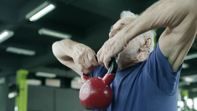 senior man working out with a kettle bell - sport video stock e b–roll