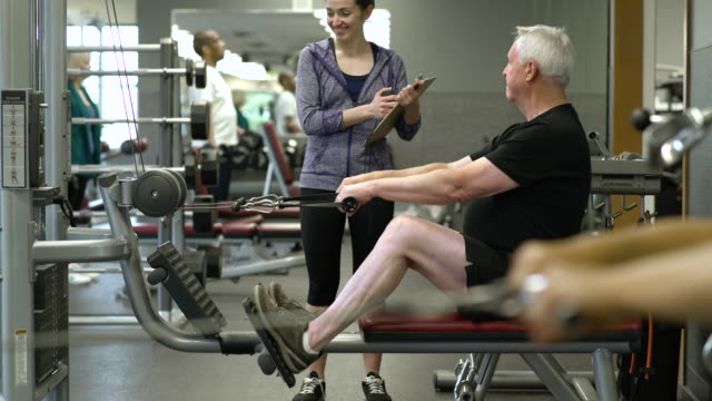 vidéos et rushes de senior man working out with a rowing machine - montrer la voie