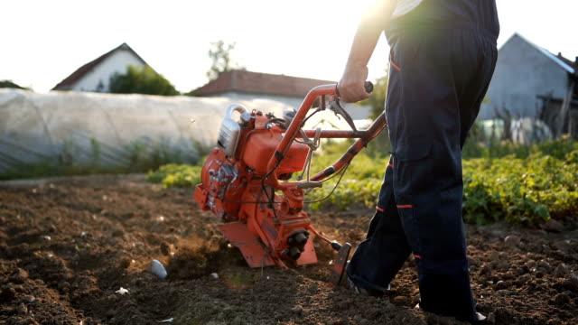 vídeos y material grabado en eventos de stock de senior hombre trabajando con cultivador - oficio agrícola