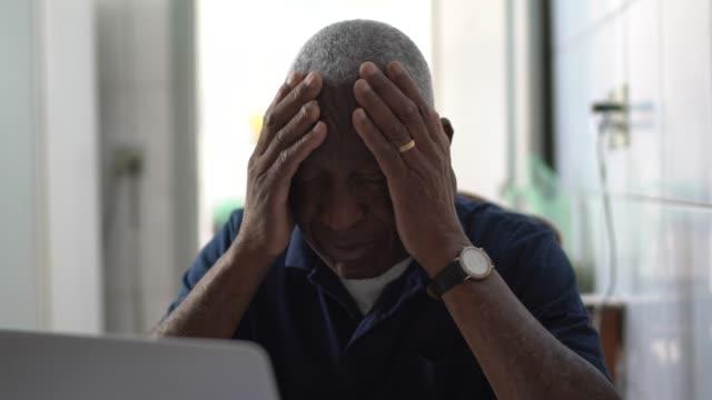 vidéos et rushes de homme aîné s'inquiétant de travailler à l'ordinateur portatif - se tenir la tête entre les mains