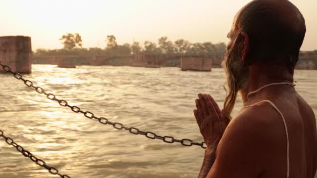 senior man worshipping at riverbank, ganges river, haridwar, uttarakhand, india - less than 10 seconds stock videos & royalty-free footage