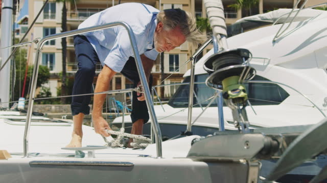 senior man wrapping rope on bollard in yacht - anchored stock videos & royalty-free footage