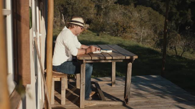 vídeos de stock, filmes e b-roll de senior man writing in notebook outside at wooden table - caderno de anotação
