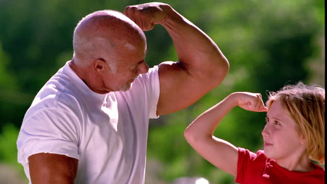 ms senior man + young girl flexing + comparing biceps outdoors - showing off stock videos & royalty-free footage