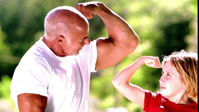 overexposed ms senior man + young girl flexing + comparing biceps outdoors - bicep stock videos and b-roll footage