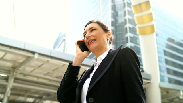 senior management woman talking by mobile phone.panning camera around her with building as background. - lead stock videos and b-roll footage