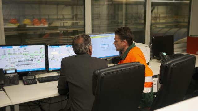 vidéos et rushes de gestionnaire principal observant des ouvriers dans la salle de contrôle de recyclage - salle de contrôle
