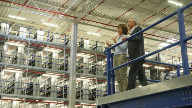 senior managers overlooking their warehouse - führungstalent stock-videos und b-roll-filmmaterial