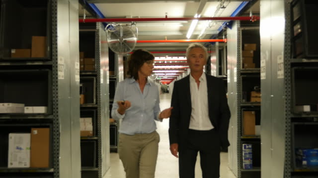 Senior managers walking the corridor of a warehouse building