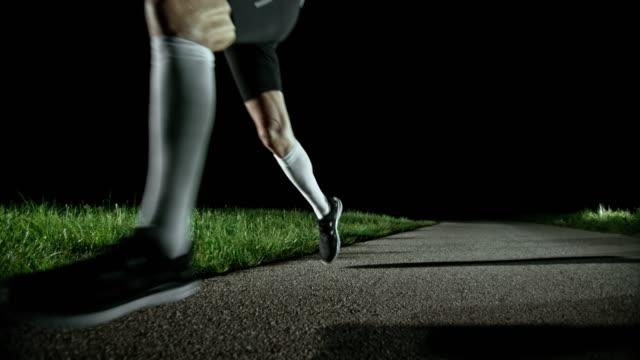 vídeos de stock, filmes e b-roll de slo mo pan terceira maratona corredor correndo à noite - camiseta