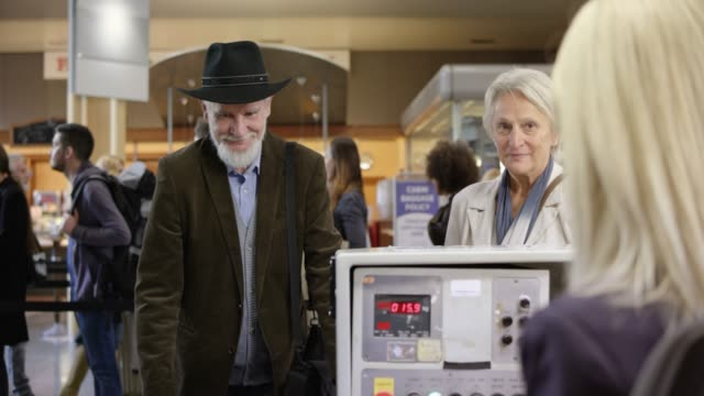 Senior married couple checking in at the check in desk at the airport