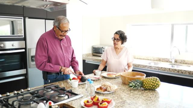 シニア結婚ラテン系カップルが自宅で朝食を準備 - サンドイッチ作り点の映像素材/bロール