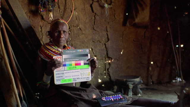 vidéos et rushes de ms senior masai tribeswoman holding clapboard in hut / kenya - acteur