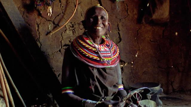 ms senior masai tribeswoman sitting in hut + smiling / kenya - waist up stock videos & royalty-free footage
