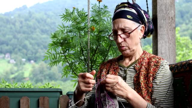 senior mature countrywoman knitting  on sofa - mature adult stock videos & royalty-free footage