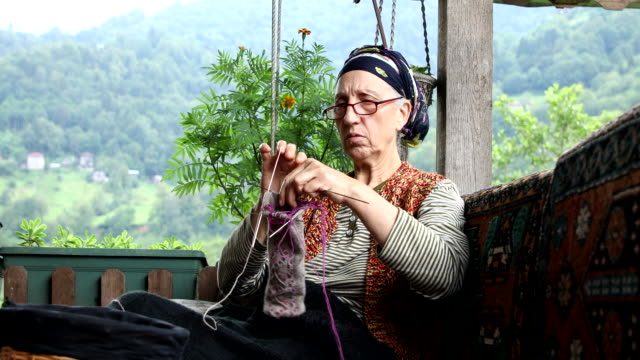 vídeos y material grabado en eventos de stock de senior madura compatriota tejiendo en el sofá - tejer