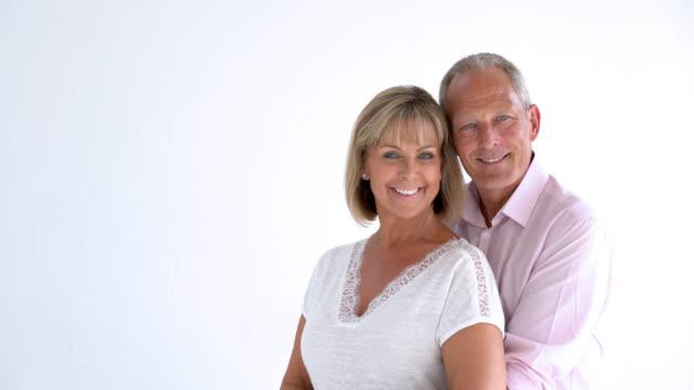 vídeos de stock e filmes b-roll de senior mature couple embracing and looking at the camera smiling - carinhoso