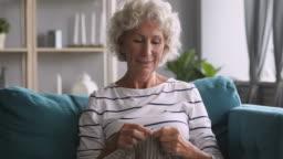 Senior mature woman knitting relaxing on sofa at home