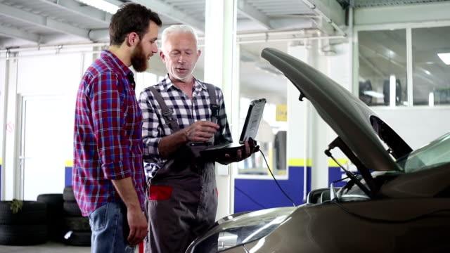 Senior mekaniker på arbete i garaget med anpassade