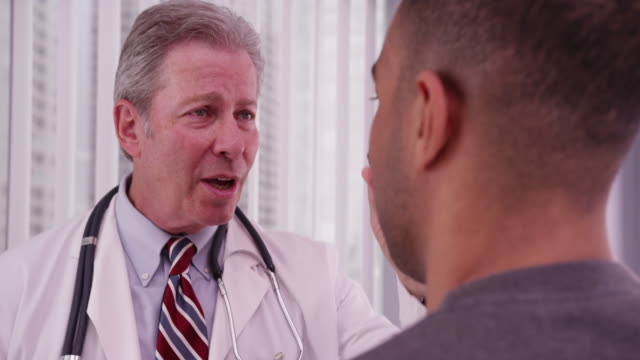 vídeos de stock, filmes e b-roll de senior medical doctor examining male african patient's eyes - physical injury