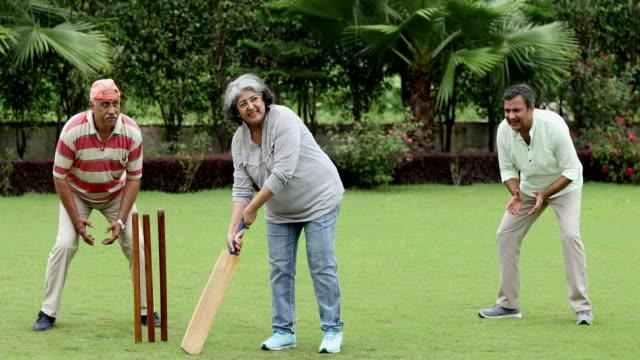 Senior men and senior woman playing cricket, Delhi, India