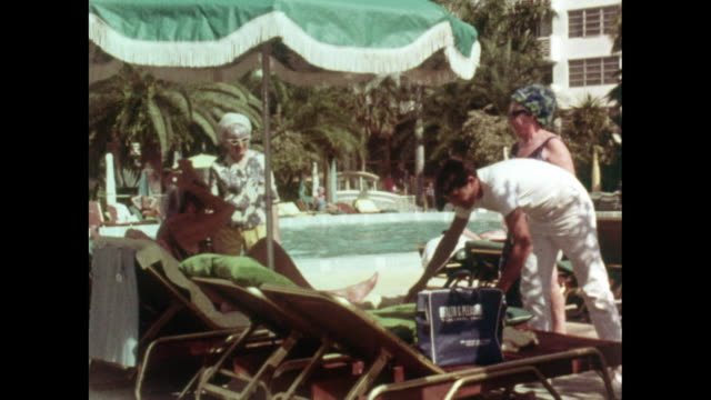 senior men and women relaxing by miami poolside; 1969 - 日光浴点の映像素材/bロール