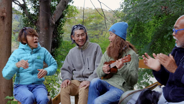 senior men and women singing to the ukulele in the sun. - only japanese stock videos & royalty-free footage