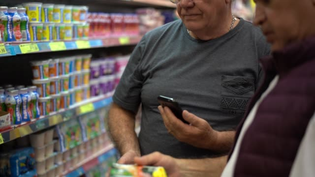 senior men buying some products in the supermarket while using smartphone - routine stock videos & royalty-free footage