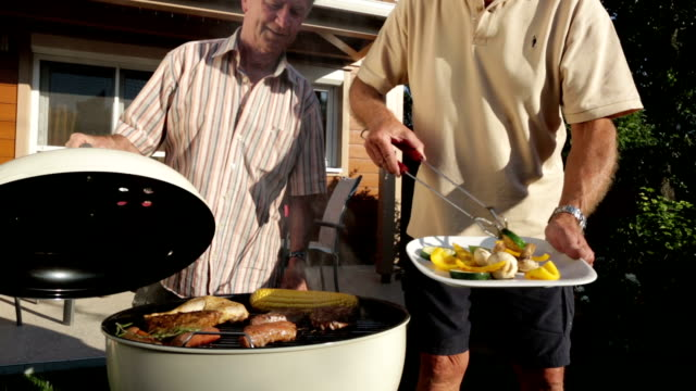 senior men cooking on barbecue grill - lid stock videos & royalty-free footage