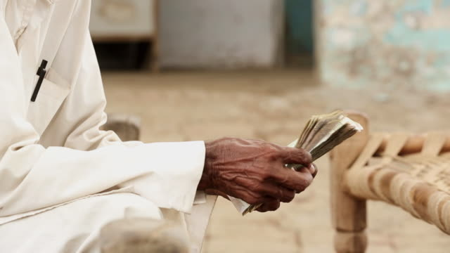 Senior men counting indian rupees, Haryana, India