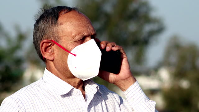 senior men covering his face with pollution mask for protection against covid-19 and talking on mobile phone - india stock videos & royalty-free footage