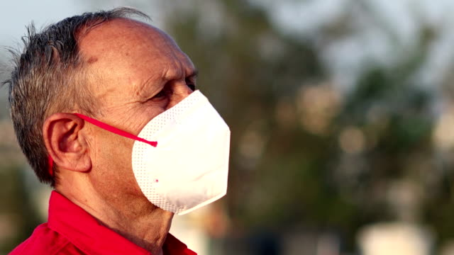 senior men covering his face with pollution mask for protection from viruses - protective workwear stock videos & royalty-free footage